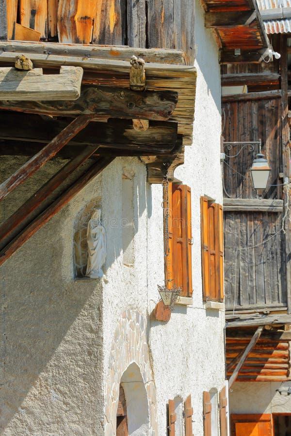 在传统木房子的特写镜头在有圣母玛丽亚一个白色雕象的圣韦朗村庄前景的 免版税库存照片
