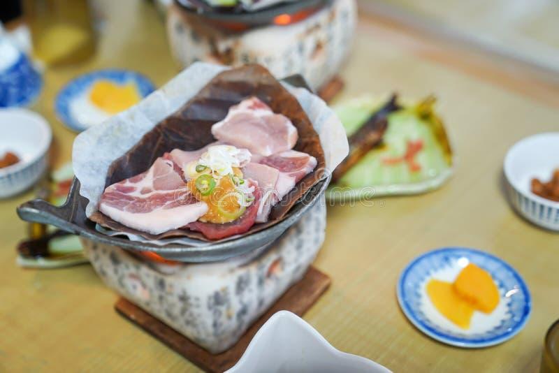 在传统火炉的日本猪肉格栅样式与地方干叶子和开胃菜 免版税图库摄影