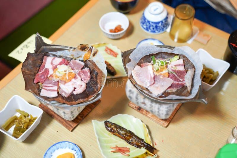 在传统火炉的日本猪肉格栅样式与地方干叶子和开胃菜 免版税库存照片