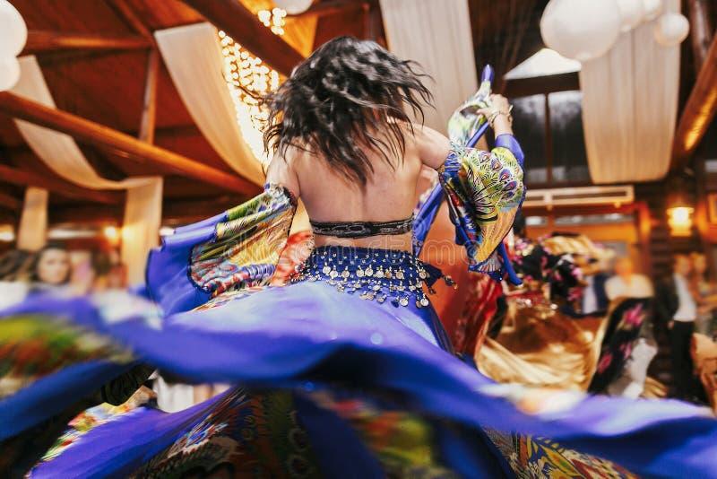 在传统蓝色花服的美好的吉普赛女孩跳舞在结婚宴会在餐馆 执行吉普赛人舞蹈的妇女 库存照片