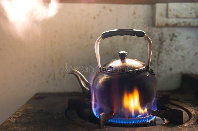 在传统金属水壶的通入蒸汽的水在煤气炉的火 免版税库存照片