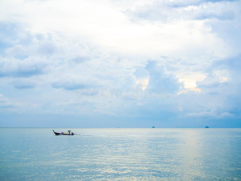 在传统长尾巴小船的小船司机在海有在日落的云彩和天空背景在泰国最低纲领派样式 免版税库存照片