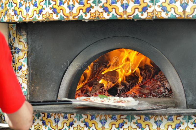 在传统wood-burning烤箱烘烤的比萨 库存图片