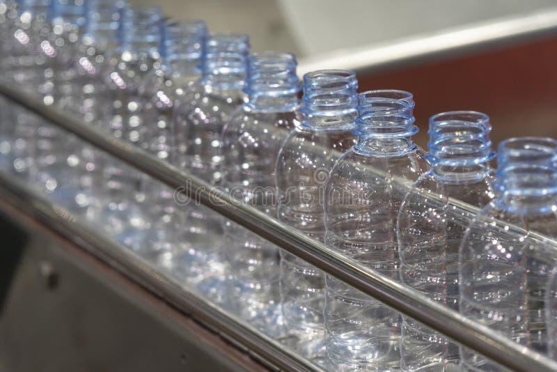 在传送带的新的宠物瓶在水装填过程 免版税库存照片