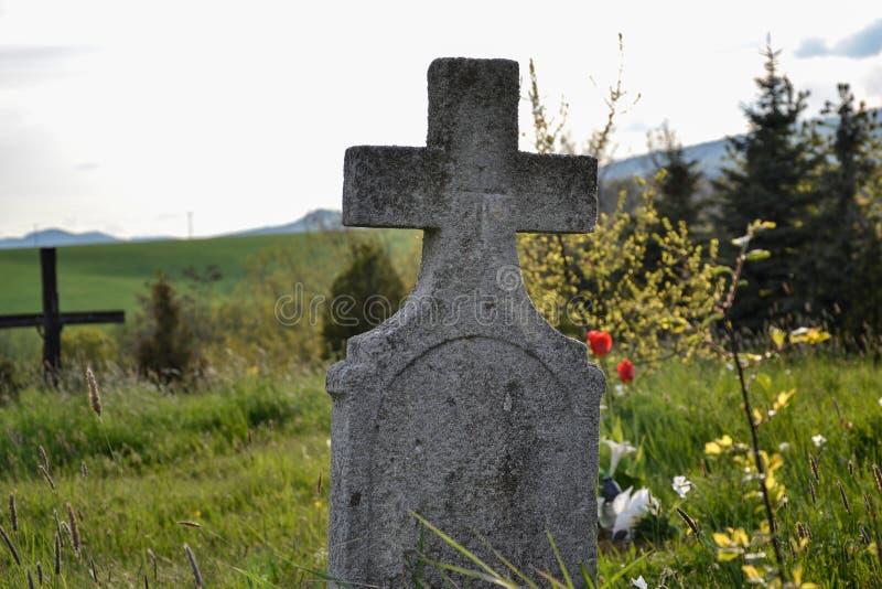 在传统欧洲公墓的老坟墓在斯洛伐克 在严重围场的年迈的发怒坟茔石头在春天 免版税库存照片