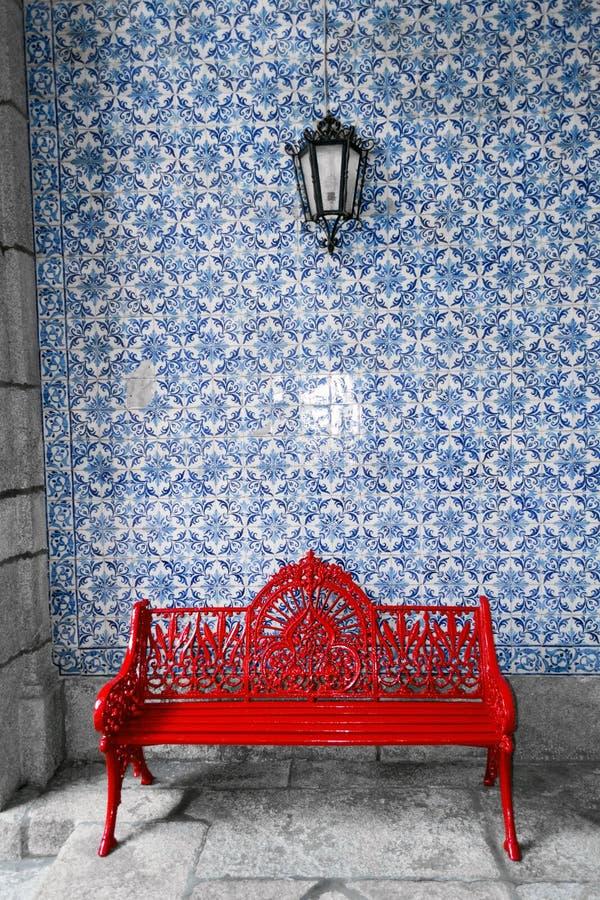 在传统葡萄牙azulejos墙壁前面的红色长凳 免版税库存图片