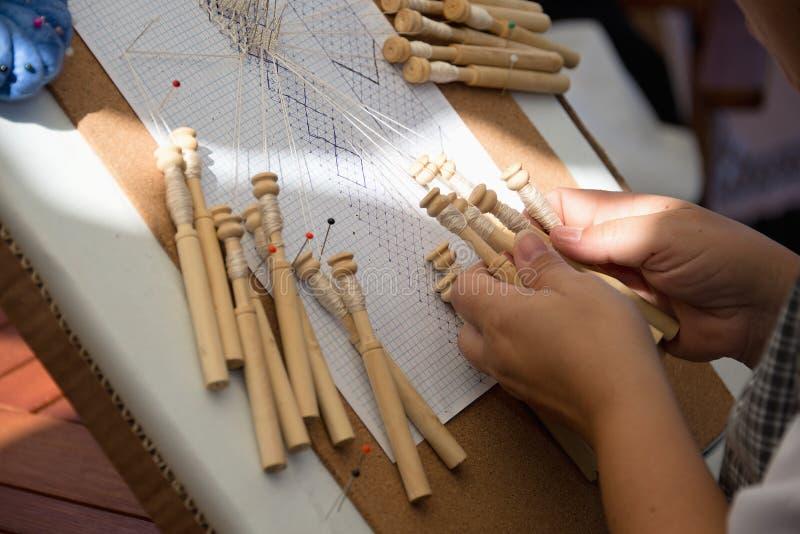 在传统鞋带制造工艺的熟练的女性手 图库摄影