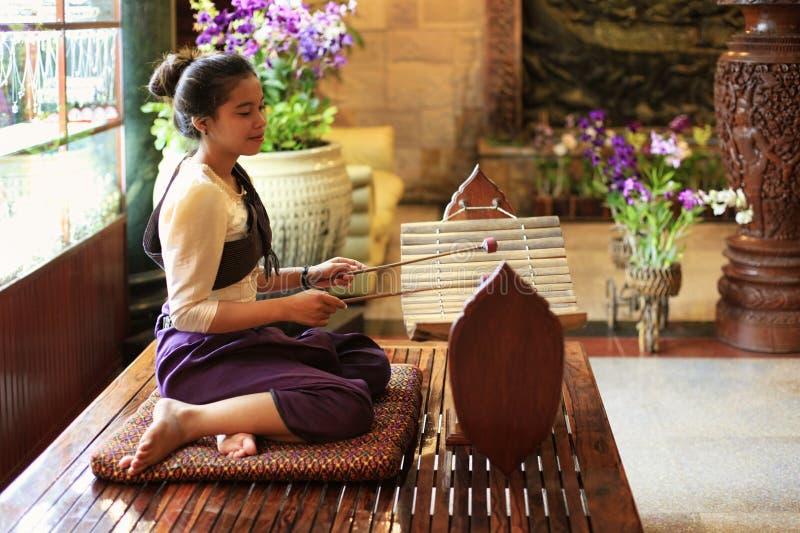 在传统gamelan仪器的女孩戏剧 免版税库存照片