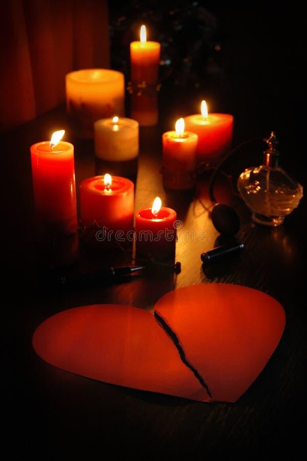 在伤心形状的情书与蜡烛和浪漫老香水瓶的 免版税库存照片