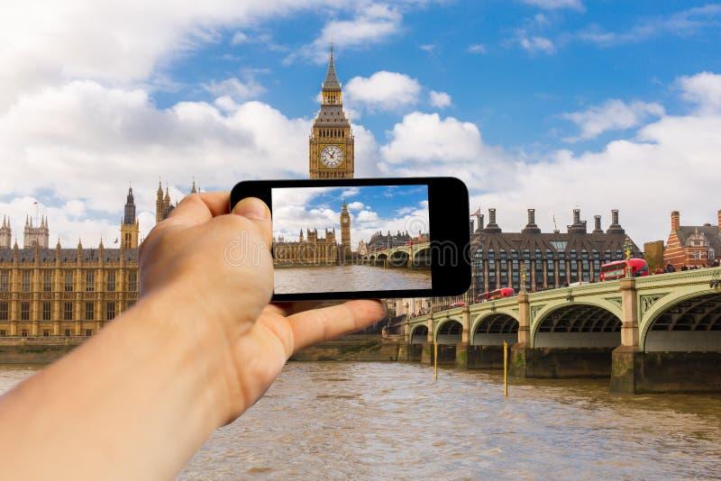 在伦敦递举行一个智能手机并且做与大本钟的一张照片 库存图片
