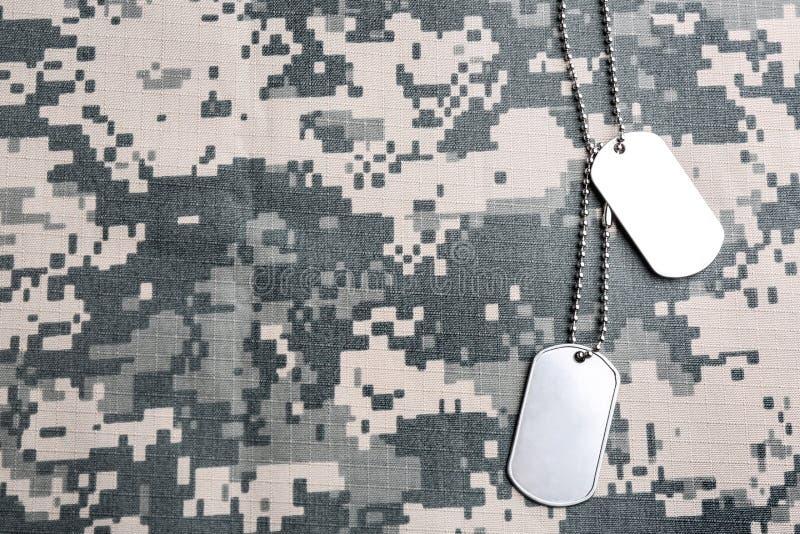 在伪装背景,顶视图的军事ID标记 免版税库存图片