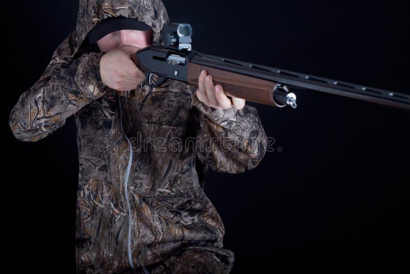 在伪装衣物的猎人有在被隔绝的黑背景的一杆枪的 有猎枪的人 一套camo衣服的年轻人与 免版税库存图片