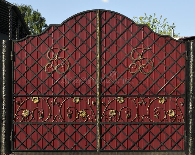 在伪造的红色门上有金组合图案和样式 库存图片