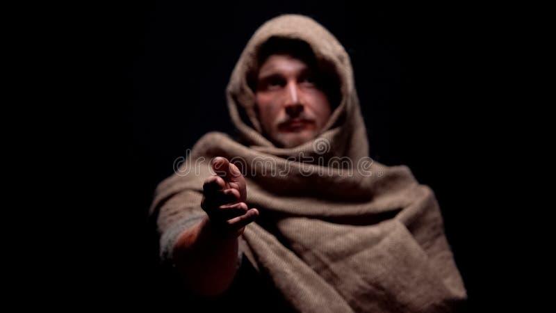 在伸手的长袍的男性请求帮助绝望的饥饿的叫化子等待的食物 免版税库存图片