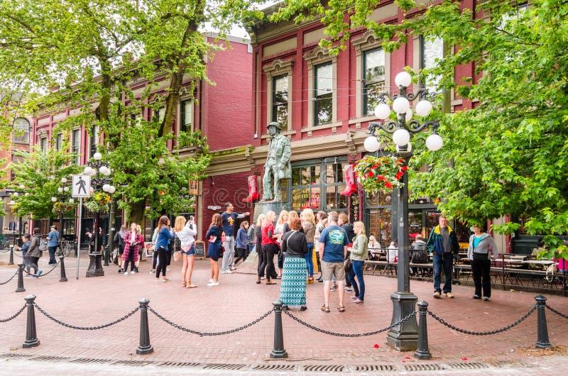 在似气体的杰克雕象前面的游人在Gastown,温哥华,加拿大 免版税库存图片