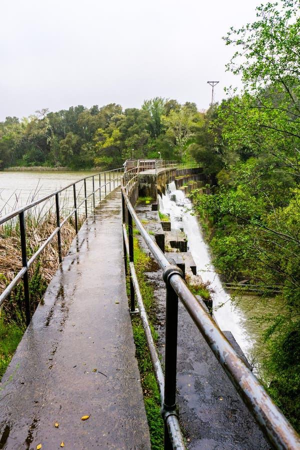 在位于碧玉里奇生物蜜饯的Searsville湖的水坝在一下雨天,旧金山湾区,加利福尼亚 免版税库存图片