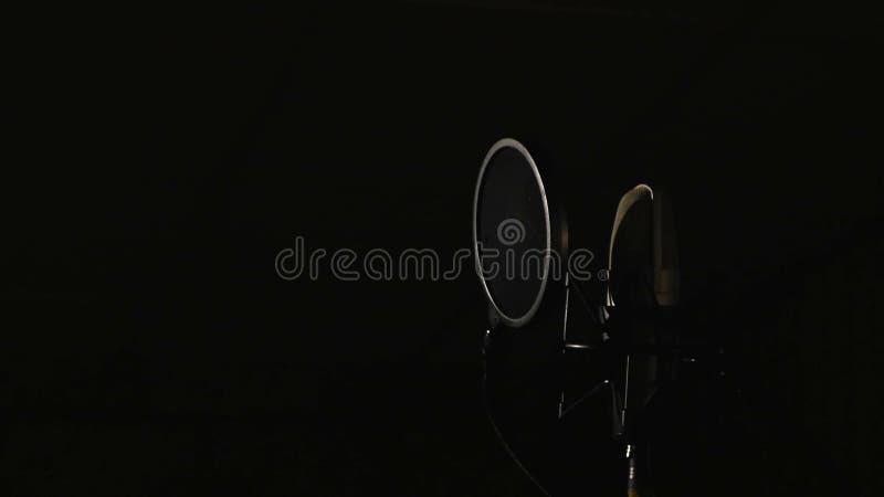 在位于音乐演播室录音摊的立场的话筒在低调光下 免版税库存照片