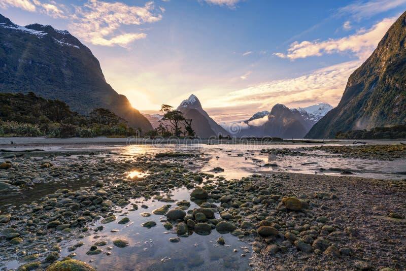 在低潮期间的日落在Milford Sound,南方,新西兰` s南岛 免版税库存照片