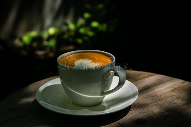 在低灯木地板自然光的拿铁咖啡设计或背景工作的 免版税库存照片