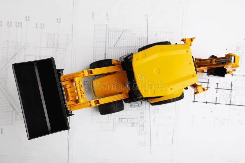 在住宅建设图纸的拖拉机玩具 免版税图库摄影