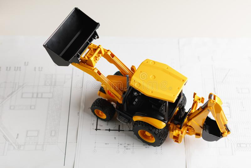 在住宅建设图纸的拖拉机玩具 库存照片
