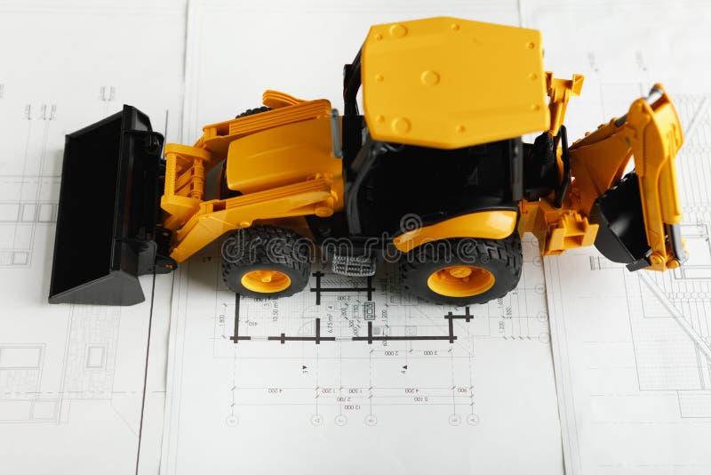 在住宅建设图纸的拖拉机玩具 库存图片