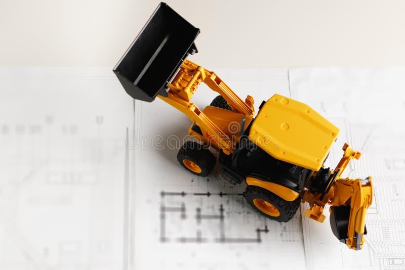 在住宅建设图纸的拖拉机玩具 免版税库存图片