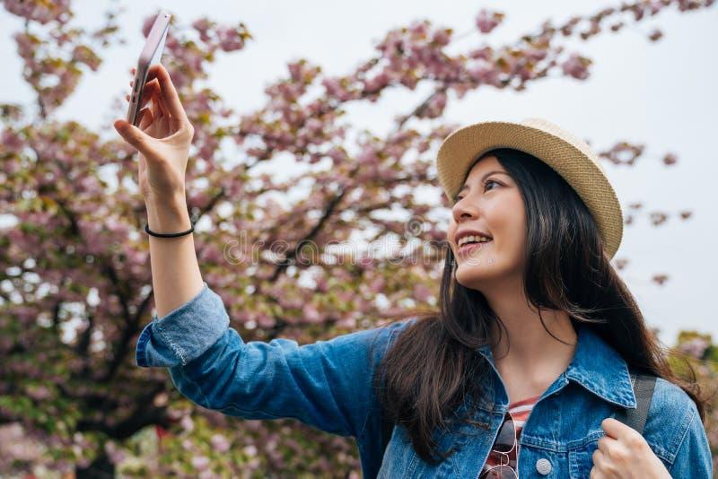 在佐仓树和照相旁边的快乐的旅客身分由手机应用程序 快乐年轻亚裔游人使用聪明 库存照片