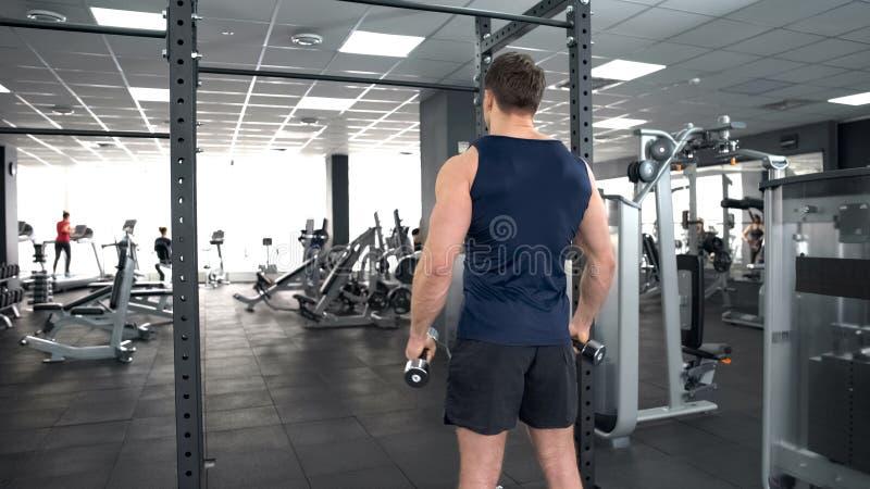 在体育俱乐部的运动员举的哑铃,侧向培养锻炼活跃休闲 免版税库存照片