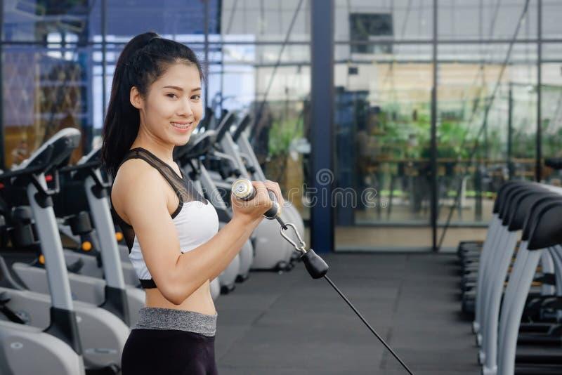 在体育健身健身房的亚洲妇女锻炼车身制造厂 免版税库存图片
