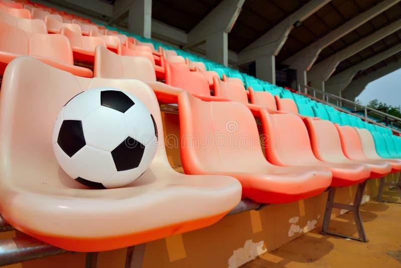 在体育场位子的足球 库存图片