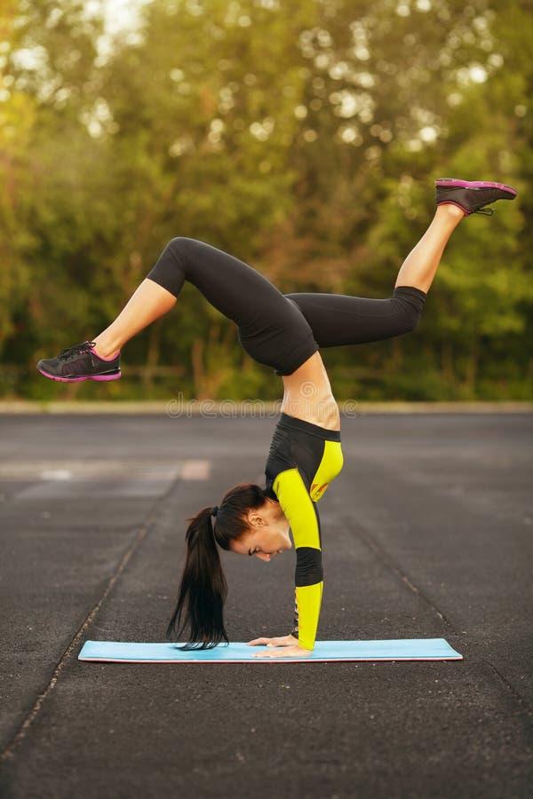 在体育场内减肥做锻炼手倒立,运动的女孩锻炼的运动妇女,户外 图库摄影