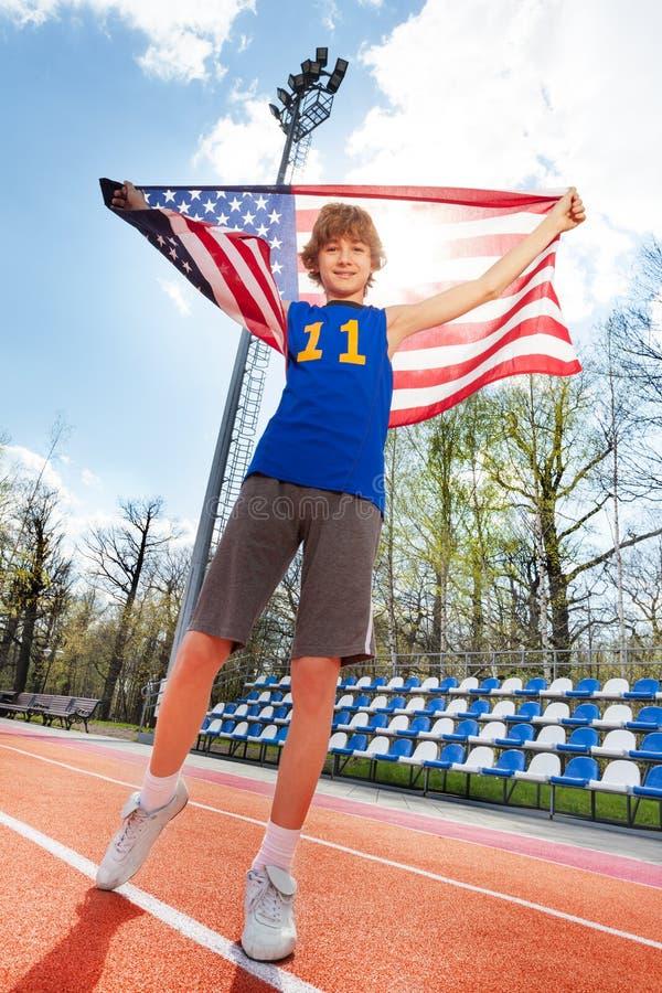 在体育场内炫耀有美国国旗的优胜者 图库摄影