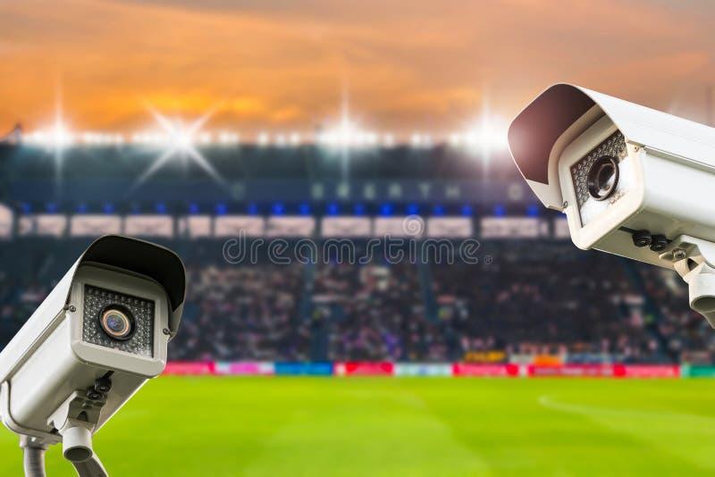 在体育场橄榄球的CCTV安全在暮色背景 库存图片