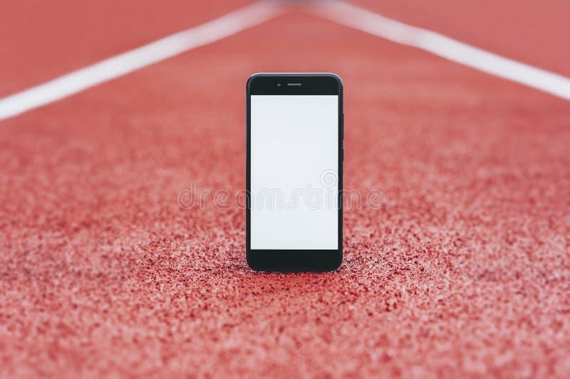 在体育场的假装智能手机跑的 在体育题目的概念  免版税图库摄影