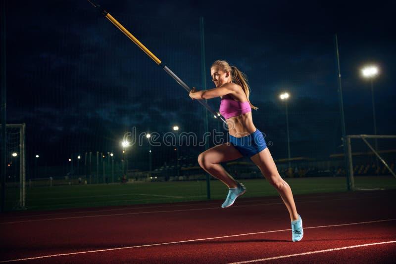 在体育场的女性撑竿跳选手训练在晚上 免版税库存图片