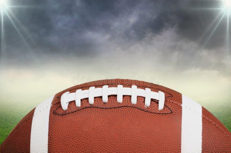 在体育场领域背景的橄榄球球 免版税图库摄影