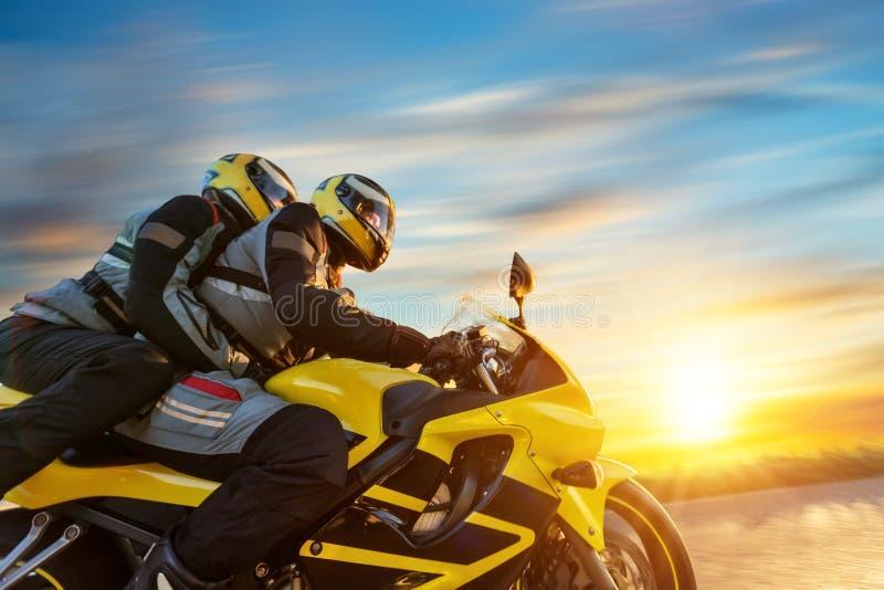 在体育摩托车骑马的Motorbikers在日落 库存照片