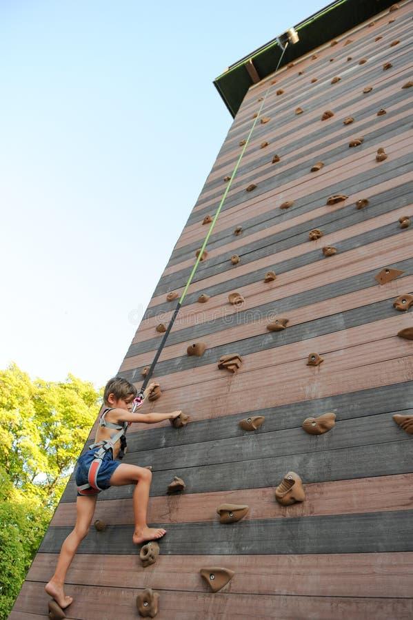 在体育操场勇敢攀登高岩石墙壁的小孩户外 图库摄影