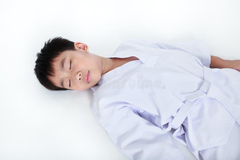 在体育的事故 亚裔儿童运动员说谎的跆拳道下来u 免版税库存图片