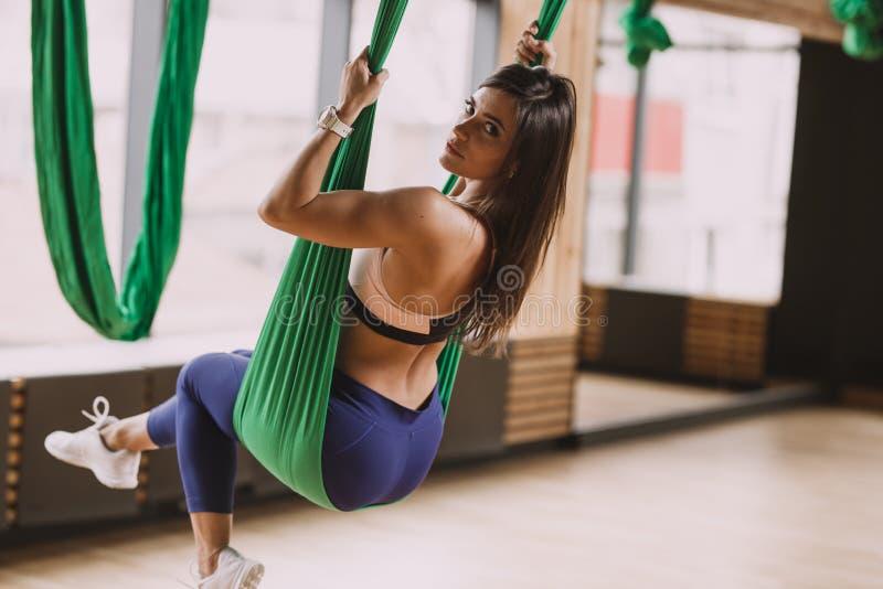 在体育衣裳打扮的美丽的年轻深色的女孩是在现代健身房的绿色空中丝绸 免版税库存图片