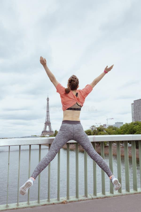 在体育衣裳的年轻女人慢跑者在巴黎,法国跳跃 库存图片