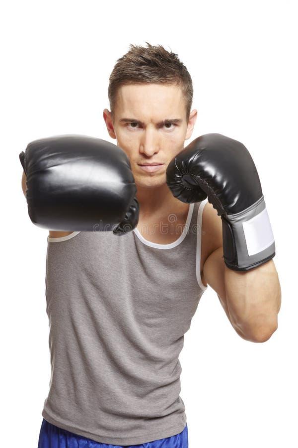 在体育运动成套装备的肌肉年轻人拳击 免版税库存图片