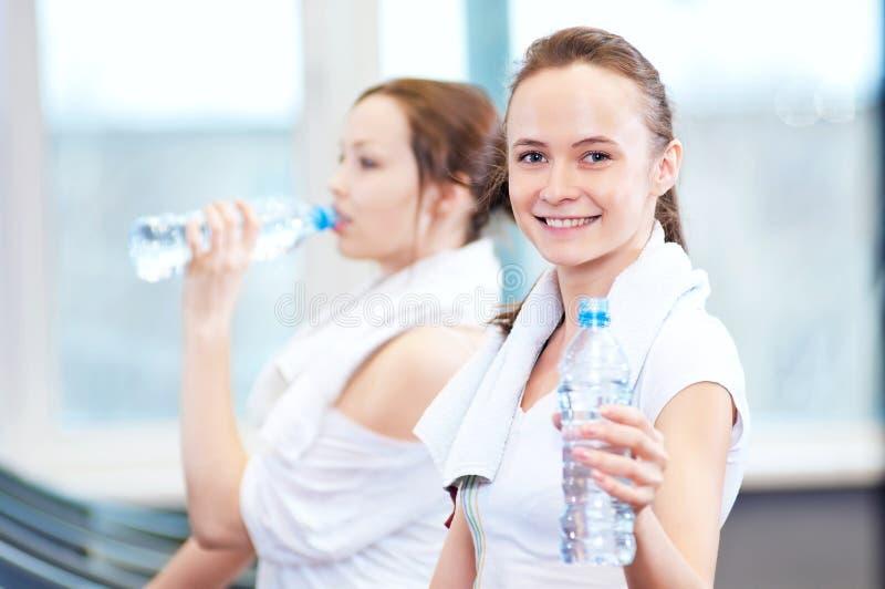 在体育运动以后的妇女饮用水 免版税库存照片