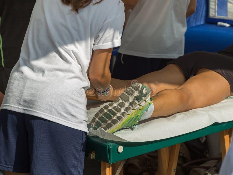 在体育锻炼以后的运动员` s小牛肌肉专业按摩治疗:健身和健康 免版税库存照片