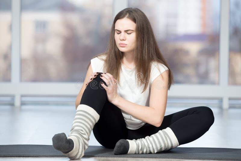 在体育锻炼期间,妇女伤害了她的膝盖 库存照片