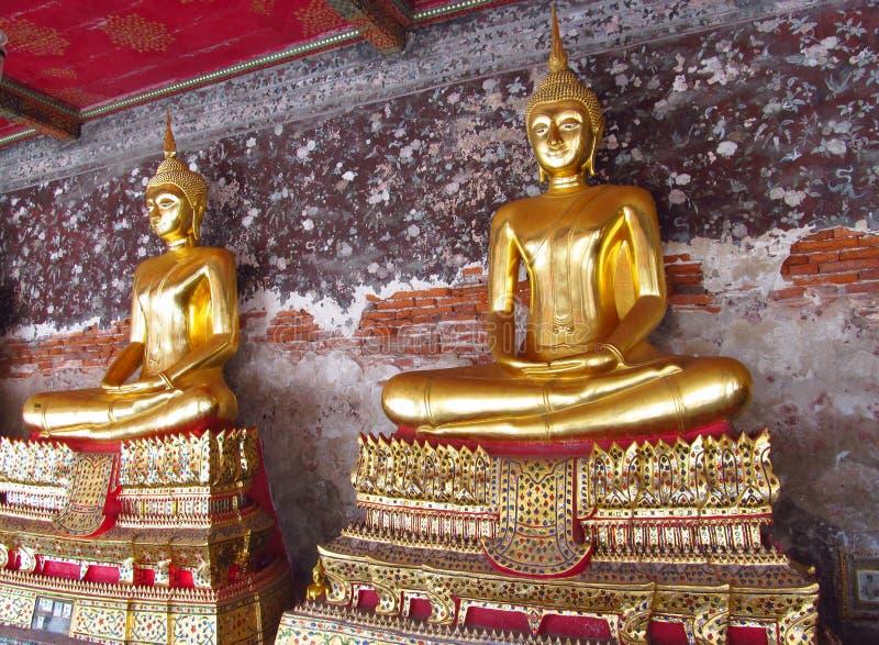 在佛教寺庙的两金色菩萨雕象 免版税库存图片
