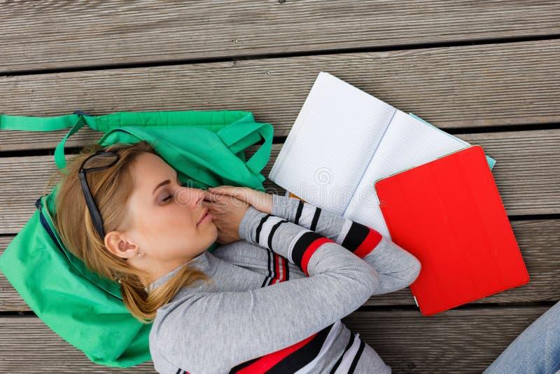 在作业簿中的睡觉的学生在木地板上 免版税库存图片