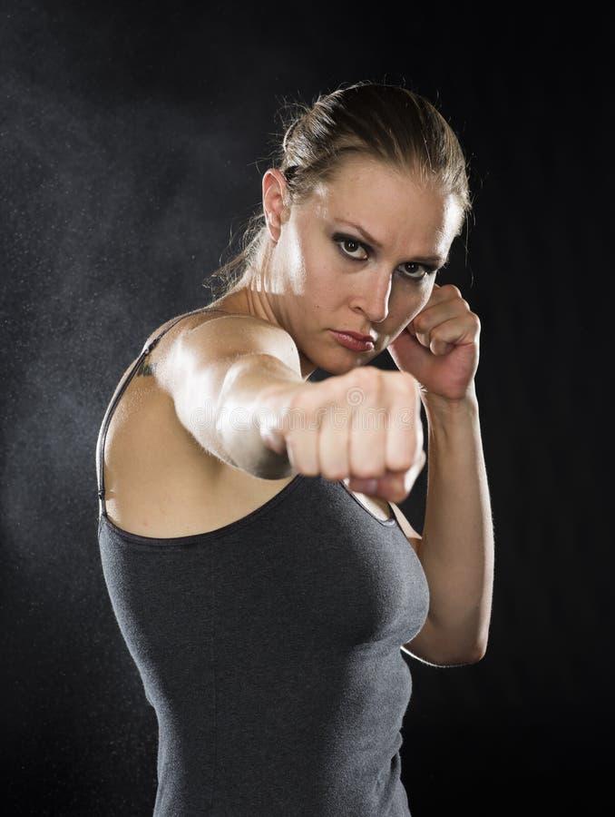 在作战姿势的女性战斗机反对黑色 免版税库存照片