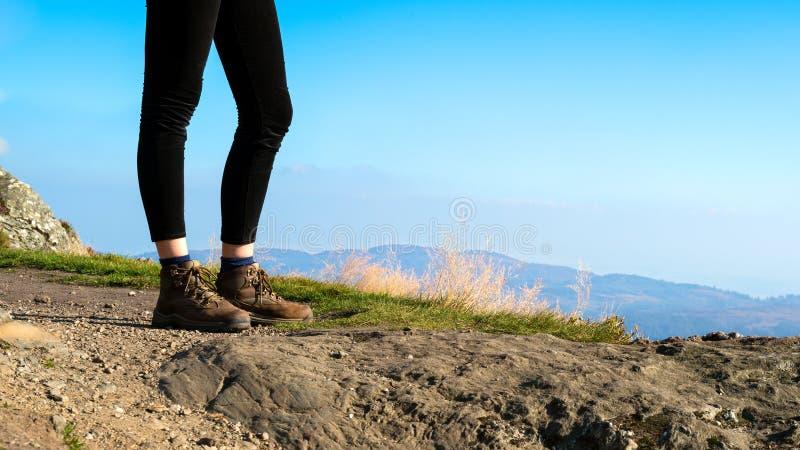 在佩带的山顶部的女性远足者远足起动 图库摄影